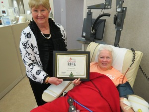 CBC Apheresis Coordinator Marilyn Staker presents a 390 LTD certificate to donor Katie Ellis.