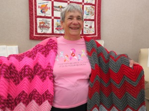 Fran Duell spreads her wings to show off her dazzling Breast Cancer Awareness pink afghan and Ohio State Buckeyes vs. Michigan afghan.